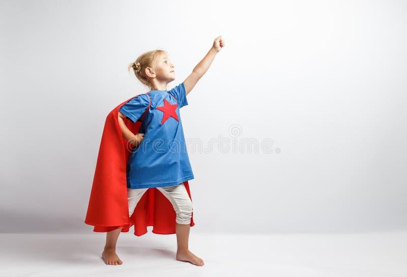La bambina si è vestita come il supereroe che sta accanto alla parete bianca immagine stock libera da diritti