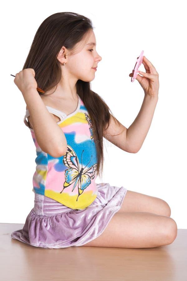 La bambina si ammira in uno specchio immagini stock