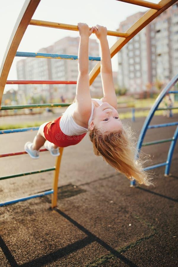 La bambina si diverte sulla barra di scimmia fotografia stock