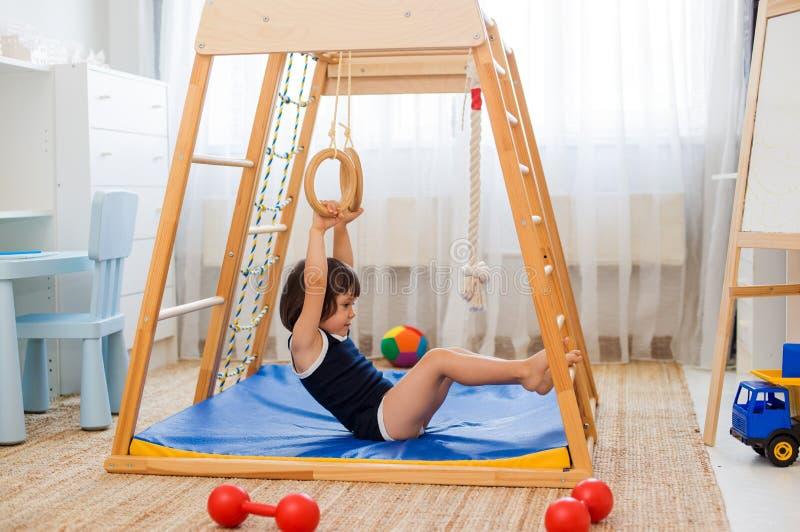 La bambina si esercita relativi alla ginnastica sull'sport domestici di legno complessi immagini stock