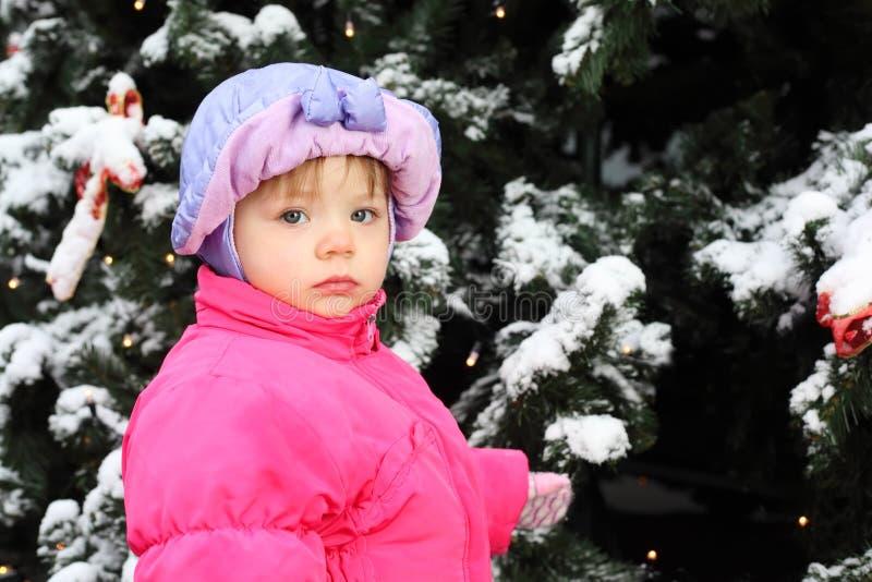 La bambina si leva in piedi vicino all'albero verde fotografia stock libera da diritti