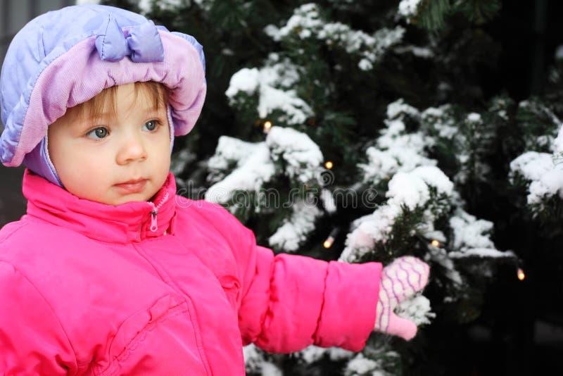 La bambina si leva in piedi vicino all'albero verde fotografie stock
