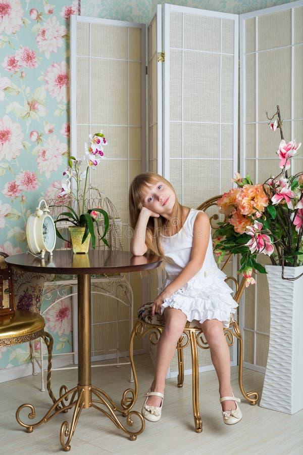 La bambina si siede ad una tavola in una stanza immagine stock