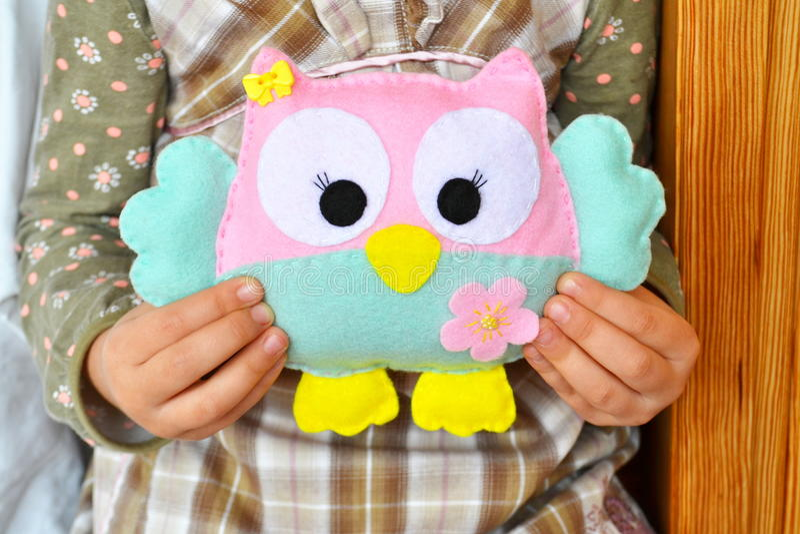 La bambina si siede e tiene un giocattolo del gufo nelle mani Giocattolo rosa e blu sveglio del feltro Decorazione del feltro del immagine stock libera da diritti