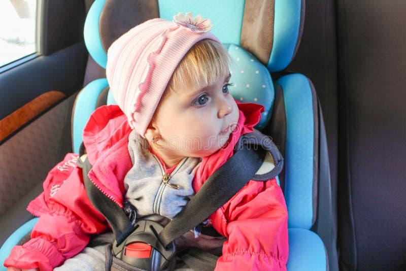La bambina si siede nella sede di automobile Il bambino guarda al lato immagine stock libera da diritti