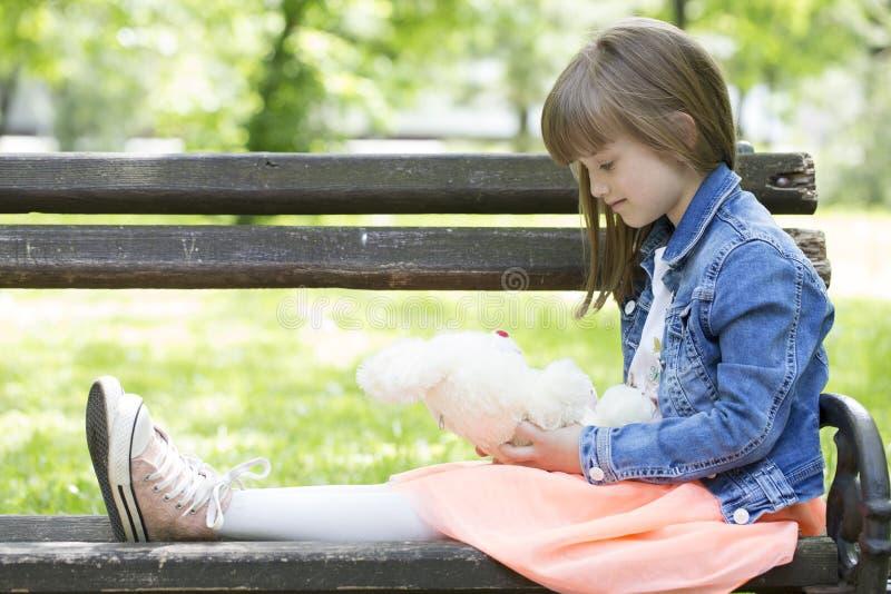 La bambina si siede su un banco e su una tenuta nelle mani del suo favo fotografia stock libera da diritti