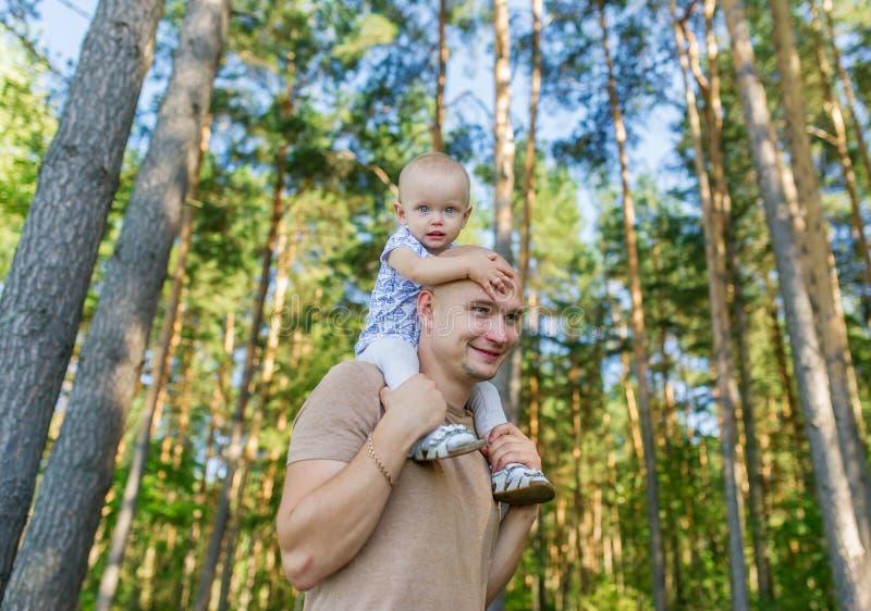 La bambina si siede sulla spalla al padre in parco in autunno fotografia stock