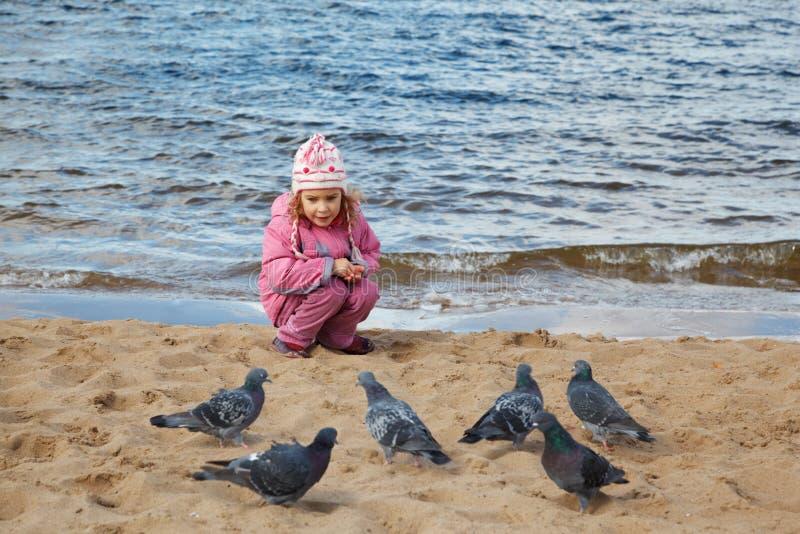 La bambina si siede sulla spiaggia al bordo dell'acqua in autunno fotografia stock