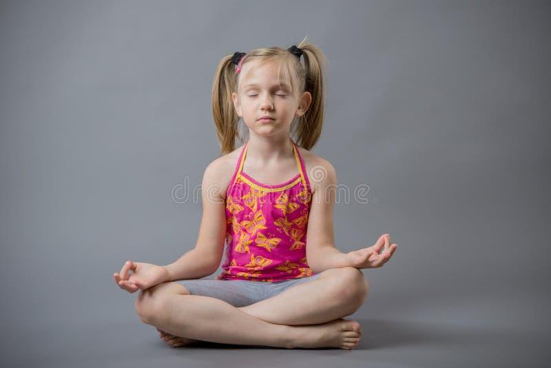 La bambina si siede in una meditazione di posa fotografia stock