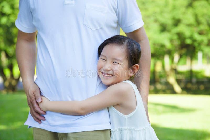 La bambina sorridente abbraccia la vita del padre nel parco fotografie stock