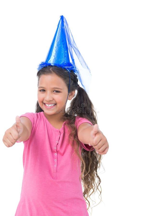 La bambina sorridente che porta il cappello blu per un partito e fa i pollici fotografia stock