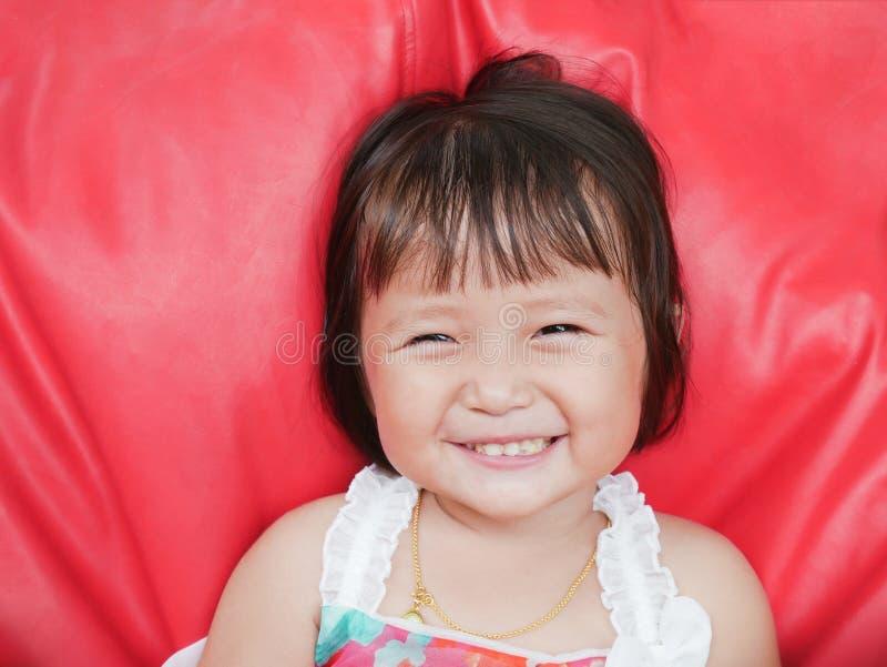 La bambina sorridente con qualcosa stucking in denti immagini stock