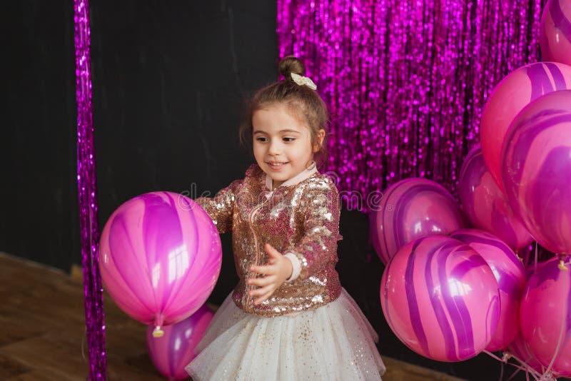La bambina sorridente gioca con i palloni rosa allo studio fotografia stock