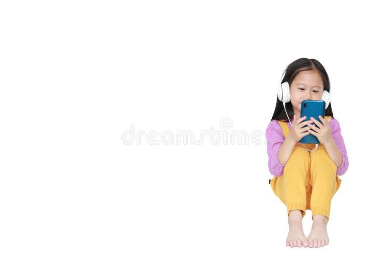 La bambina sorridente gode di di ascoltare la musica con le cuffie isolate su fondo bianco con lo spazio della copia immagini stock libere da diritti