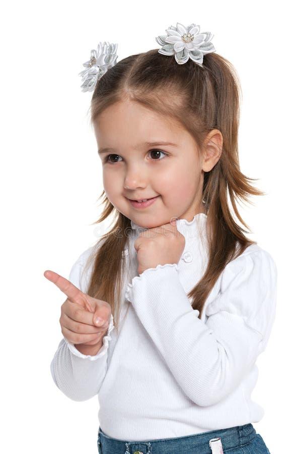 La bambina sorridente mostra il suo dito al lato immagine stock