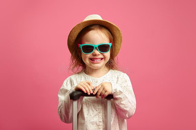 La bambina sorridente in occhiali da sole e cappello di paglia, tenenti la valigia sul rosa isolato, esprime francamente la gioia fotografia stock