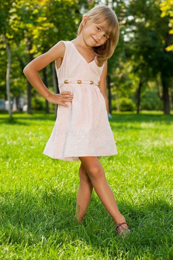 La bambina sorridente si leva in piedi nella sosta fotografie stock