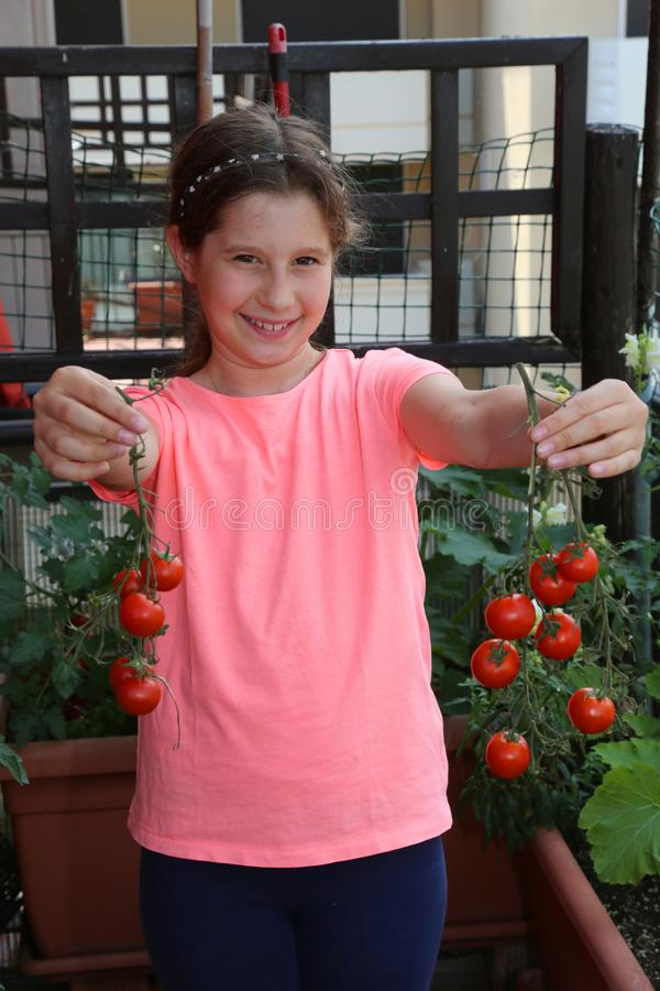 La bambina sorridente sul terrazzo della sua casa mostra il pomodoro rosso fotografia stock