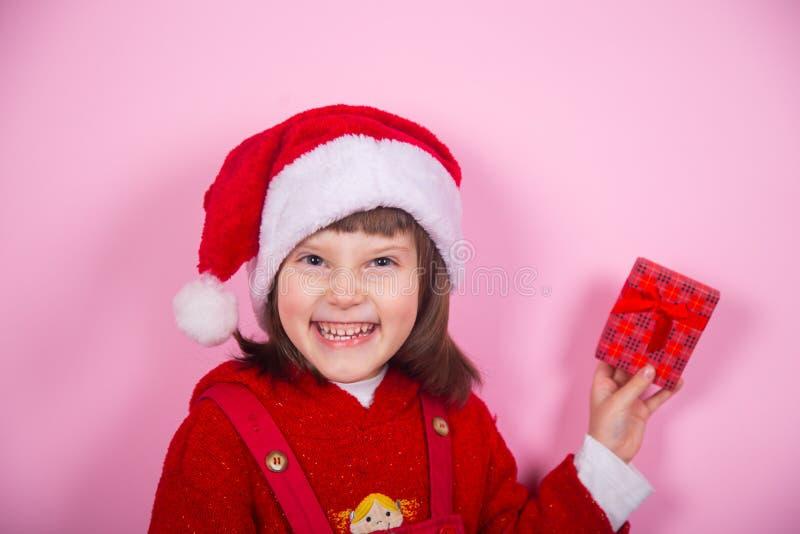 La bambina sorridente sveglia in cappello di Santa ed il Natale costume la tenuta del contenitore di regalo rosso in studio su fo immagini stock