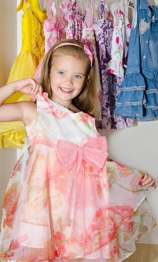 La bambina sorridente sveglia sceglie un vestito dal guardaroba fotografia stock libera da diritti