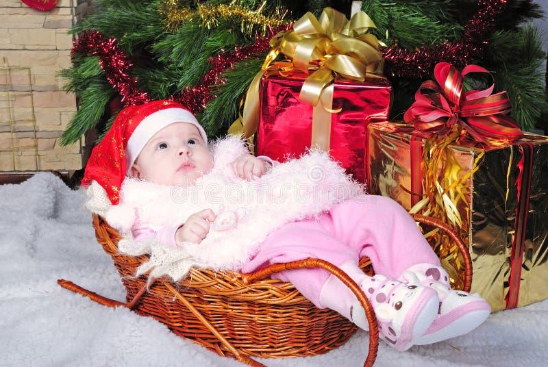 La bambina sotto l'albero di Natale sul cappuccio del nuovo anno immagine stock