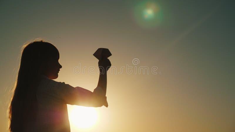 La bambina spensierata sta giocando con un aeroplano di carta al tramonto Bello chiarore della lente nel telaio fotografia stock libera da diritti