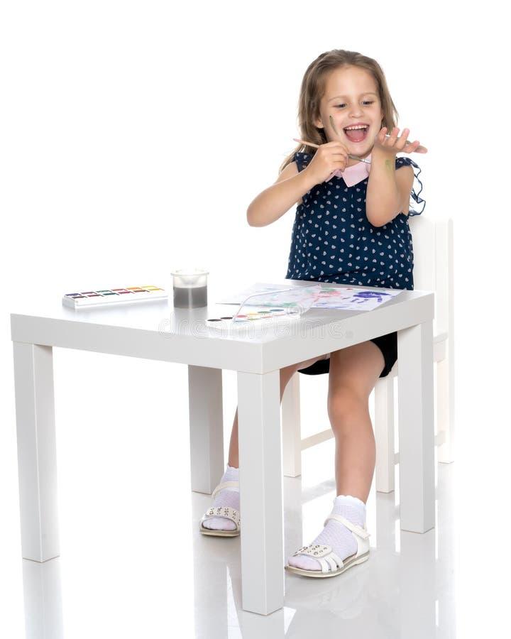 La bambina sporcata con le pitture fotografia stock