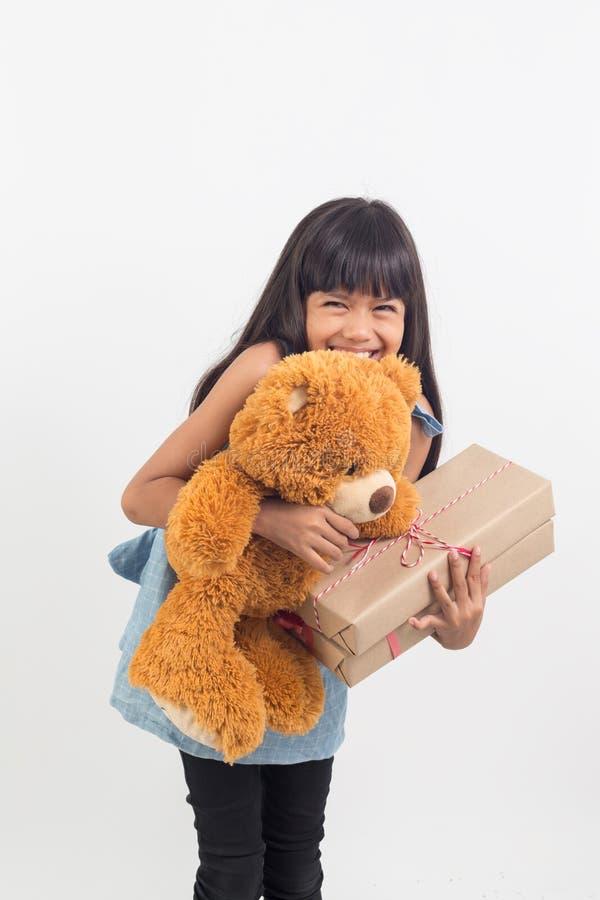 La bambina sta abbracciando un orsacchiotto con il contenitore di regalo immagini stock libere da diritti