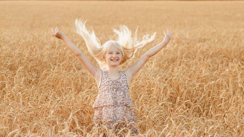 La bambina sta giocando con i suoi capelli in un campo con grano immagini stock