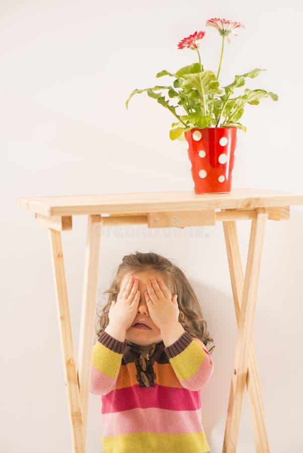 La bambina sta giocando il fronte nascondentesi di hide-and-seek immagini stock