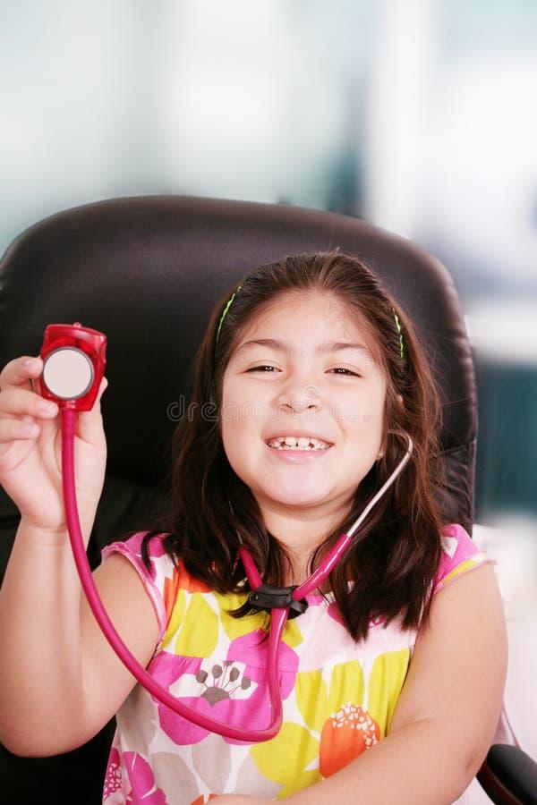 La bambina sta giocando il medico con lo stetoscopio fotografie stock libere da diritti