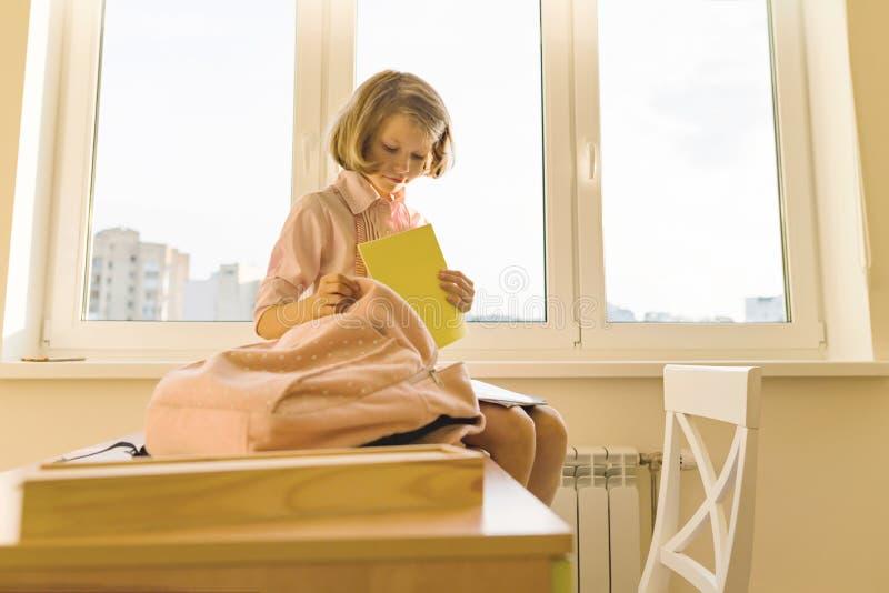 La bambina sta imballando il suo zaino della scuola che si siede sullo scrittorio Scuola, istruzione, conoscenza e bambini immagine stock