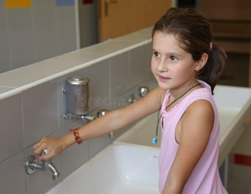 La bambina sta lavando le sue mani nel bagno della scuola immagini stock libere da diritti