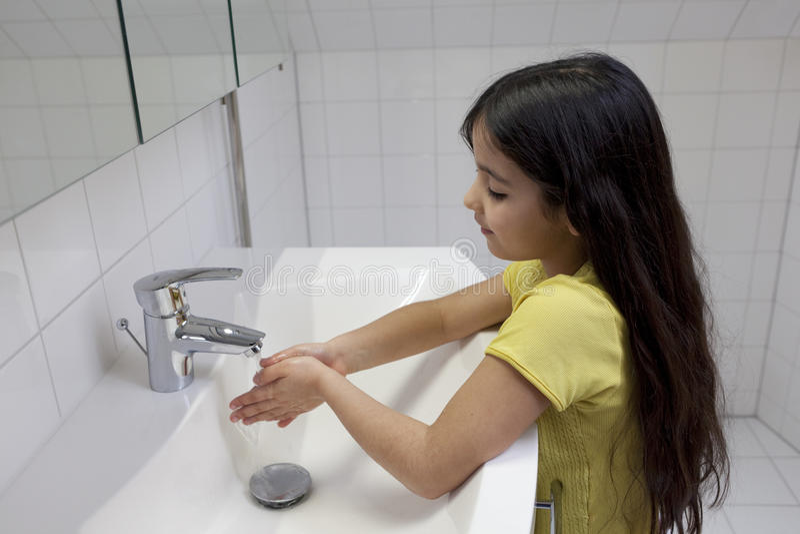 La bambina sta lavandosi le sue mani fotografia stock