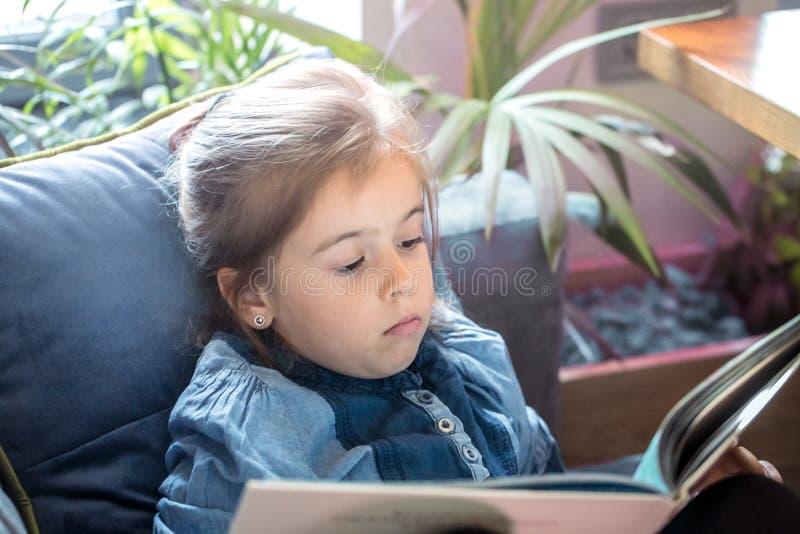 La bambina sta leggendo un libro nel salone sullo strato immagini stock
