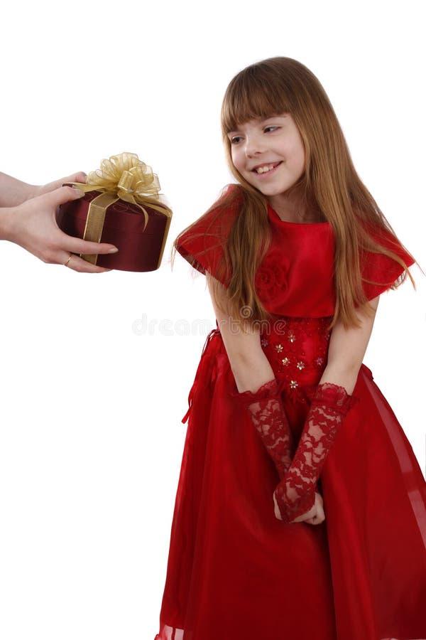 La bambina sta ottenendo il regalo. La ragazza ritiene timida. immagini stock