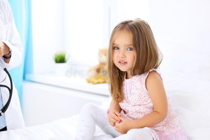 La bambina sta ritenendo il dolore mentre medico la esamina in ospedale fotografie stock libere da diritti
