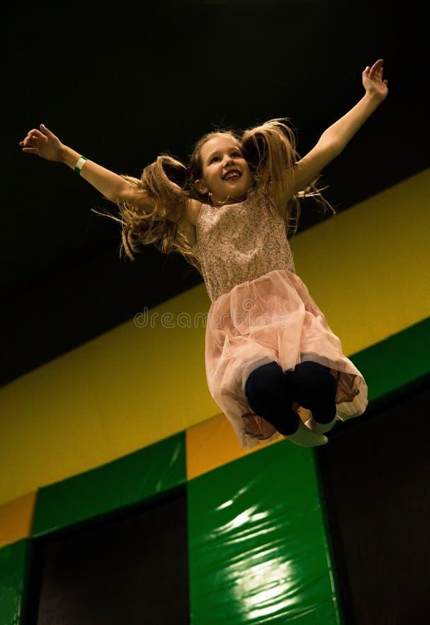 La bambina sta saltando su un trampolino in bambini gioca la stanza sul suo compleanno fotografia stock