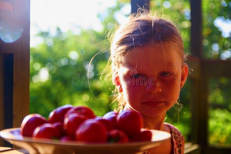 La bambina sta sedendosi ad una tavola su una veranda e sui pomodori freschi eatting immagine stock
