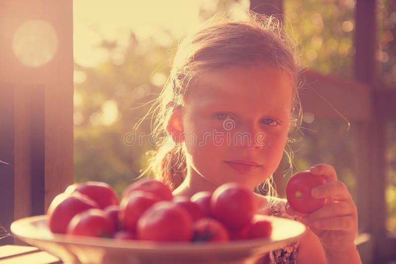 La bambina sta sedendosi ad una tavola su una veranda e sui pomodori freschi eatting fotografia stock