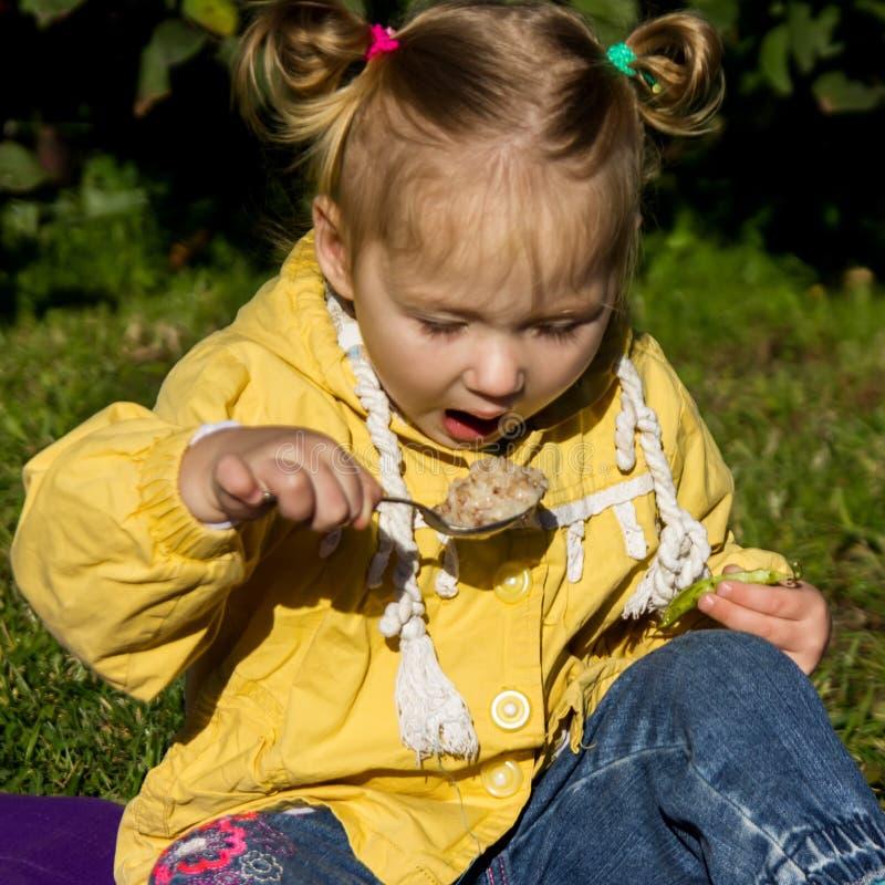 La bambina sta sedendosi su un'erba e sta mangiando il porridge immagine stock libera da diritti