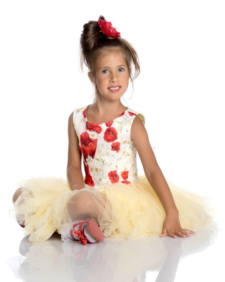 La bambina sta sedendosi sul pavimento fotografie stock libere da diritti