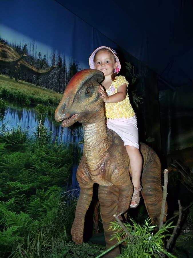 la bambina sta sedendosi sulla cima del dinosauro del giocattolo fotografia stock libera da diritti