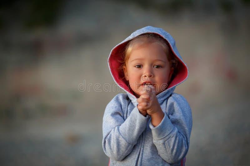 La bambina sta stando con le sue mani afferrate e sta elemosinando per compiere il suo desiderio fotografia stock libera da diritti