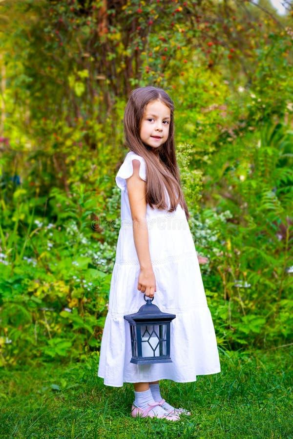 La bambina sta stando nel giardino e sta tenendo una lanterna immagini stock libere da diritti