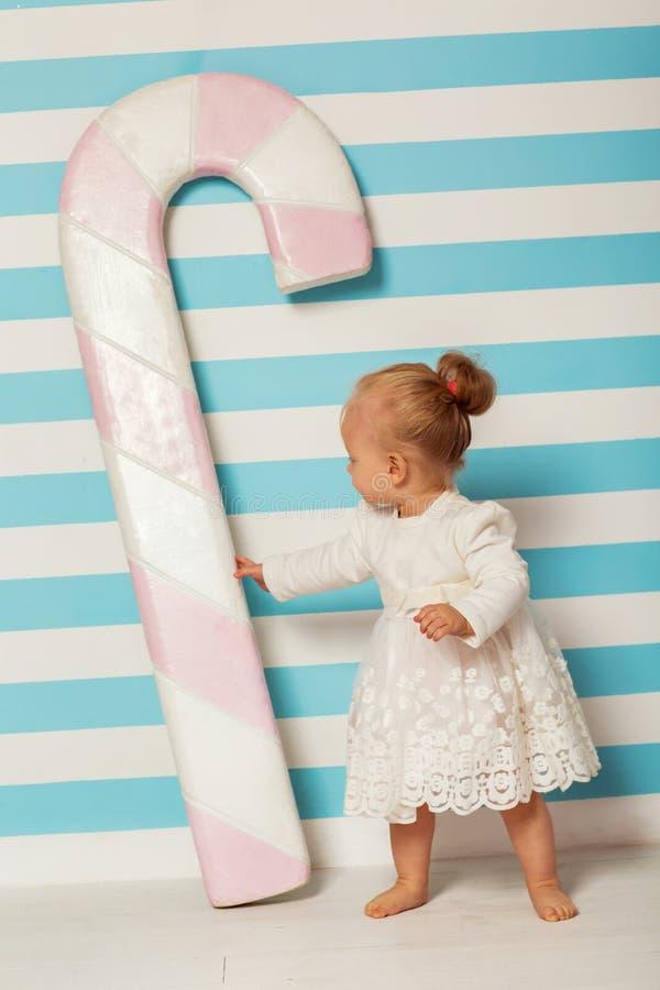 La bambina sta vicino ad un fondo a strisce con una grande caramella fotografie stock
