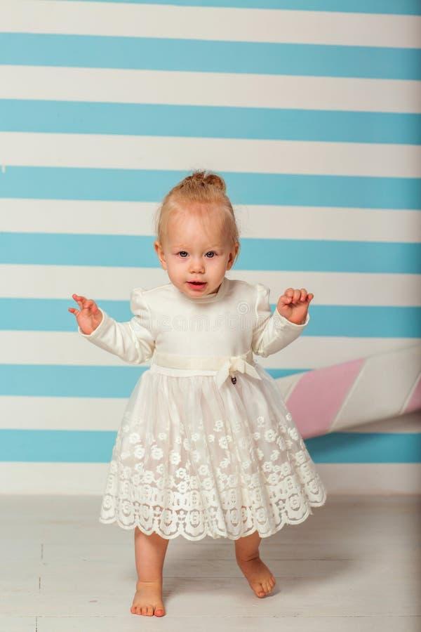 La bambina sta vicino ad un fondo a strisce con una grande caramella immagini stock libere da diritti