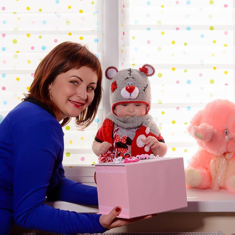 La bambina stupefacente si siede sulla finestra ed esamina il regalo ricevuto fotografie stock libere da diritti