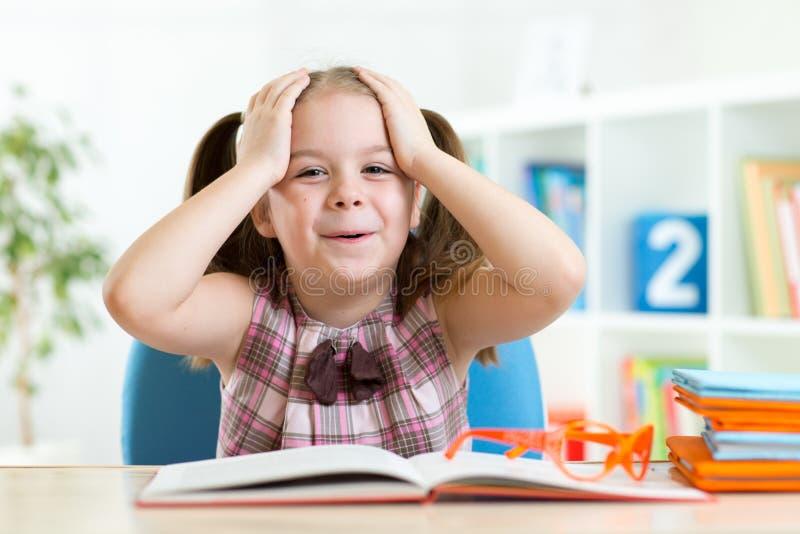La bambina stupita sta leggendo un libro fotografia stock libera da diritti