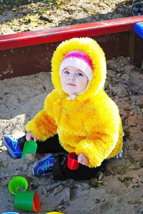 La bambina su un campo da gioco per bambini gioca la sabbia fotografia stock libera da diritti